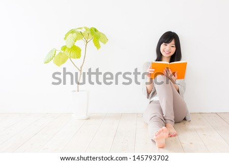 attractive asian woman reading book in the room - stock photo