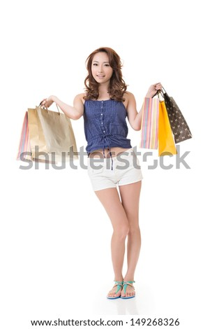Attractive Asian woman shopping and holding bags, full length portrait isolated on white background.