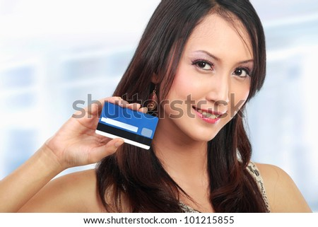 attractive asian woman showing  credit card for shopping
