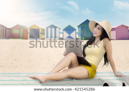 Attractive asian woman using a laptop while daydreaming on the beach - stock photo
