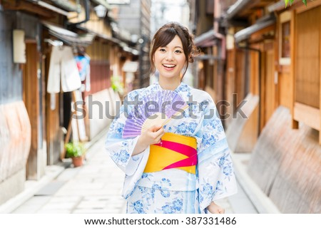 attractive asian woman wearing kimono walking on the old street