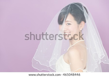 attractive asian woman wearing wedding dress isolated on purple background