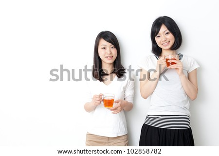 attractive asian women drinking tea in the living room - stock photo