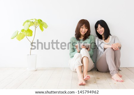 attractive asian women using tablet computer in the room - stock photo