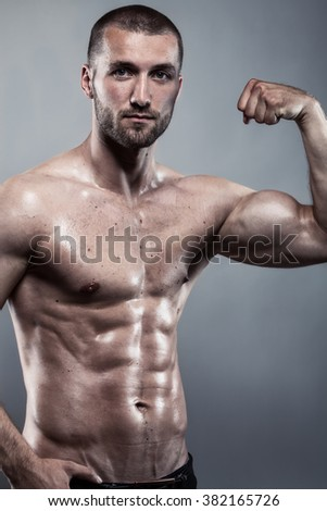 Attractive athlete with strong biceps and perfect abs