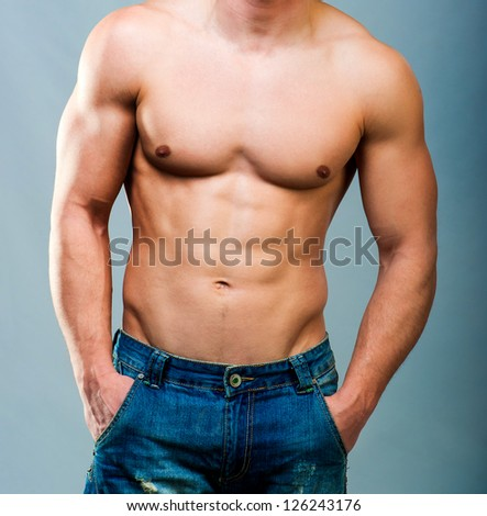 attractive athletic male torso on a gray background - stock photo