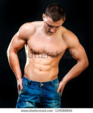 attractive athletic man on a black background - stock photo