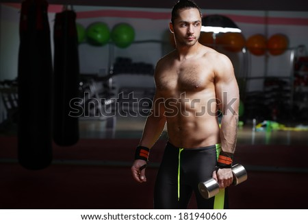 Attractive athletic man with dumbbell, in gym - stock photo