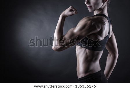 Attractive athletic woman showing biceps on a dark background - stock photo