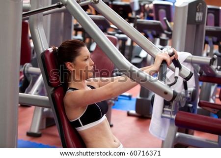 Attractive athletic woman using a bench press in a fitness center - stock photo