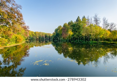 Attractive autumn landscape with beautiful woods in red, green and yellow, small wooden bridge on the horizon and great reflection of autumn foliage and trees over lake