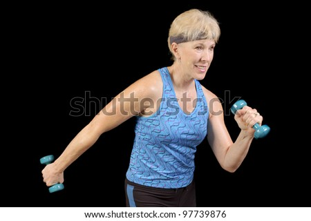 Attractive baby-boomer exercising with weights isolated over black - stock photo