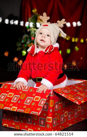 Attractive baby in Santa costume and deer hat - stock photo