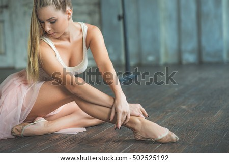 Attractive ballet dancer sitting on floor