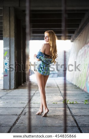 Attractive barefoot woman posing in shirt outdoors - stock photo