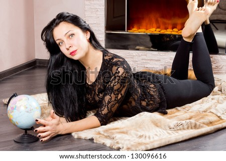 Attractive barefoot young woman lying in front of the fire with a globe in front of her dreaming of her summer vacation and travels