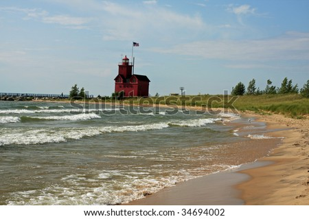Attractive beach and red lighthouse on Lake Michigan, near Holland, Michigan - stock photo