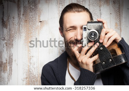 Attractive bearded man is photographing with interest. He is holding camera near his eye and smiling. The guy is standing near wall. Copy space in left side - stock photo