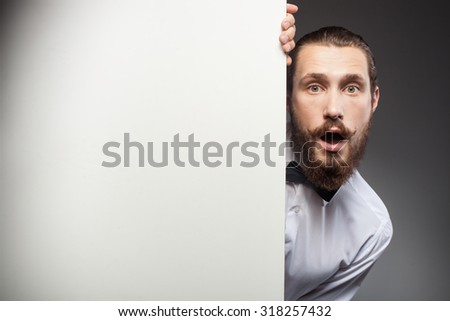 Attractive bearded man is standing behind white empty placard. He is peeking through it and looking at the camera with surprise. His mouth and eyes are wide open. Isolated - stock photo