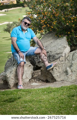 Attractive bearded man on a golf course in sunny day