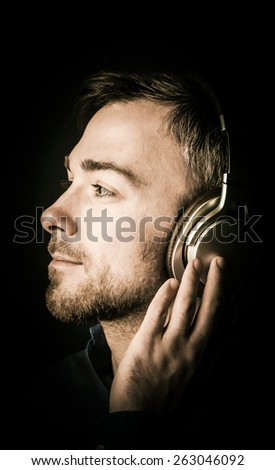 Attractive bearded young man musing as he listens to his music on stereo headphones looking off to the left in profile with a serene dreamy expression, close up of his face on a dark background