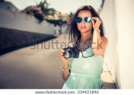 Attractive, beautiful and sexy girl taking a photograph during holidays. Outdoor photo. - stock photo