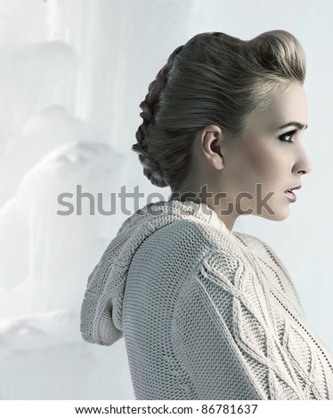 attractive beautiful blonde with a nice up do wearing a comfortable woolen sweater - stock photo