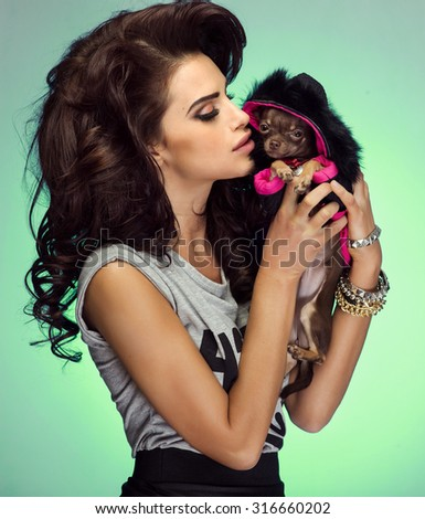 Attractive beautiful brunette woman with long curly hair posing in studio, holding little sweet dog. - stock photo