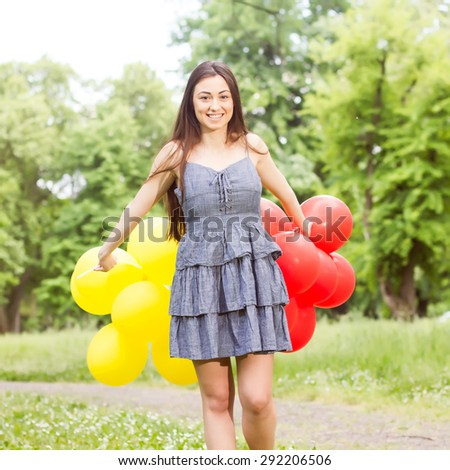 Attractive Beautiful Carefree Young Woman with Red and Yellow Balloons. Attractive caucasian female enjoying nature. - stock photo