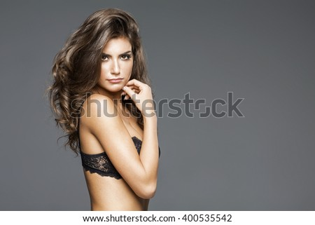 Attractive beautiful woman in lingerie posing. Girl with long curly hair - stock photo
