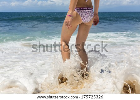 Attractive beautiful young woman in swimsuit goes into the ocean in hot summer day. Rear view  - stock photo