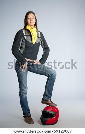 Attractive biker leans red motorbike helmet - stock photo