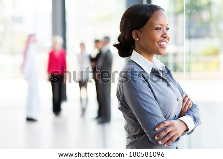 attractive black businesswoman looking outside window - stock photo