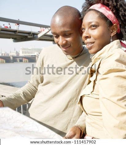 Attractive black couple looking at a guide map on vacation while standing by the Millennium Bridge in London's river Thames. - stock photo