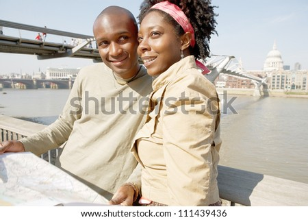 Attractive black couple looking at a guide map on vacation while standing by the Millennium Bridge and St Paul's Cathedral in London's river Thames. - stock photo