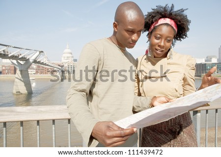 Attractive black couple looking at a guide map on vacation while standing by the Millennium Bridge and St Paul's Cathedral in London's river Thames.