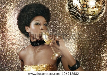 Attractive black woman drinking champagne in a nightclub and drinking champagne next to a disco ball. - stock photo