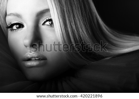 Attractive blond beauty in theatrical jabot. Black-white close-up portrait.