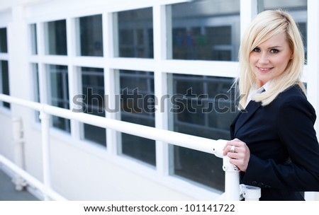 Attractive blond businesswoman holding a rail in front of a corporate building with multiple diminishing white framed windows - stock photo