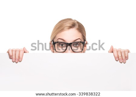 Attractive blond businesswoman looking over top of white sign with copy space isolated on white background