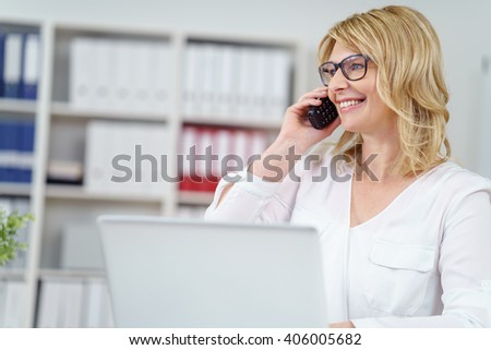 Attractive blond businesswoman wearing eyeglasses taking a call on her mobile with a smile as she sits working on a laptop in the office - stock photo
