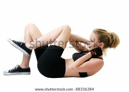 Attractive blond caucasian woman laying on floor wearing workout attire doing stomach crunches or sit ups over white - stock photo