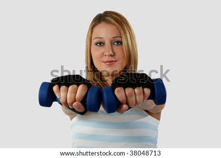 Attractive blond caucasian woman wearing workout attire with hands forward holding two three pound blue weights - stock photo