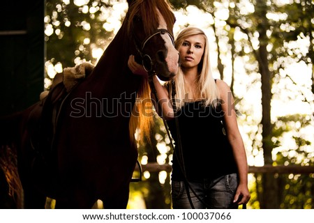 Attractive blond female with horse - stock photo