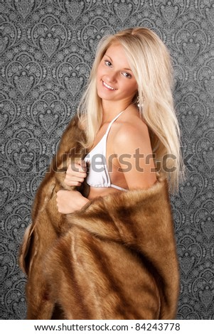 Attractive blond girl in a fur coat - stock photo
