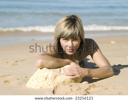Attractive blond girl laying on the beach - stock photo