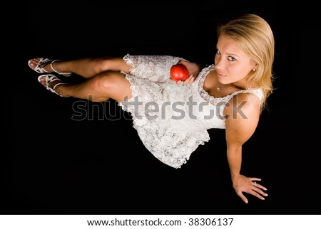 Attractive blond girl with red apple over black background - stock photo