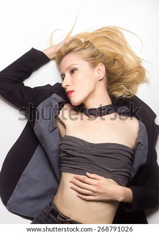 Attractive blond girl with red lipstick, laying on white background.