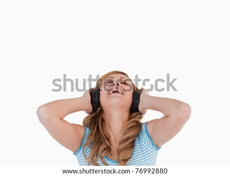 Attractive blond-haired woman happy while listening to music standing on a white background