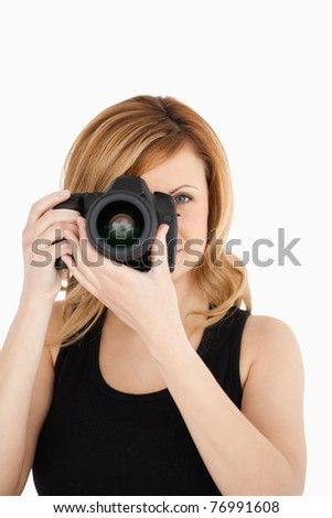 Attractive blond-haired woman taking a photo with a camera on a white background